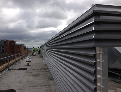 Men inspecting silver louvres on a rooftop